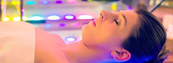 mulher deitada com diversas luzes em sessão de cromoterapia