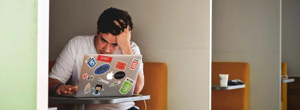 Jovem irritado em frente ao computador, com alto cortisol - burning out