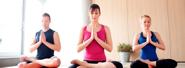 grupo praticando meditação em posição de lótus