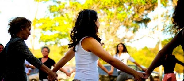mulheres em roda de mãos dadas em dança circular