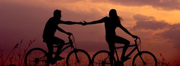 casal andando juntos de bicicleta em por do sol: relacionamentos da geração índigo