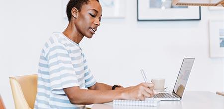 terapeuta sentada em mesa, com notebook, planejando seu marketing
