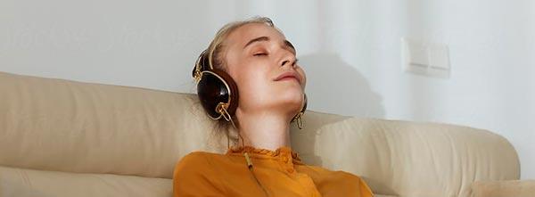 menina fazendo atendimento terapêutico online em casa, no sofá com meditação guiada