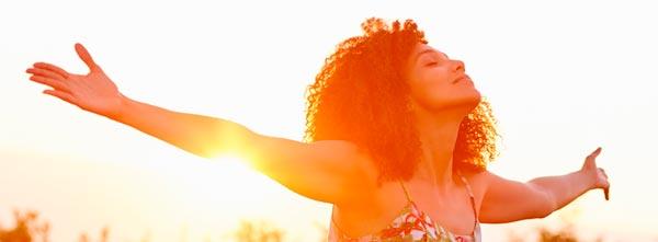 mulher de braços abertos ensolarada recebendo energia reiki