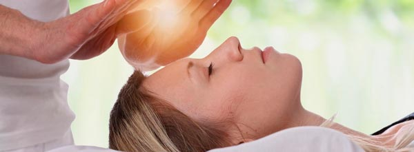 mulher deitada recebendo energia reiki durante sessão