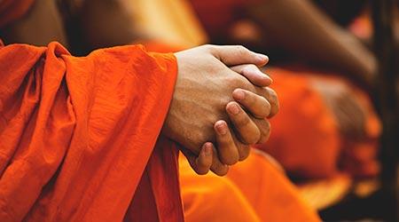 mãos de monge orando, em túnica laranja - Brahmacharya - celibato