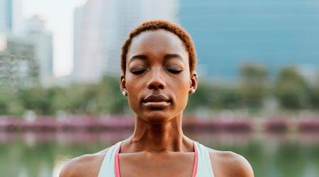 muher negra de olhos fechados meditando leve - praticando aparigraha nos pensamentos