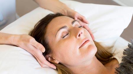 sessão de barras de access - terapeuta tocando pontos da cabeça de mulher deitada