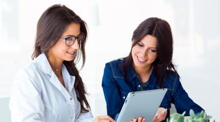 terapeutas mulheres conversando com tablet sobre programas de fidelidade
