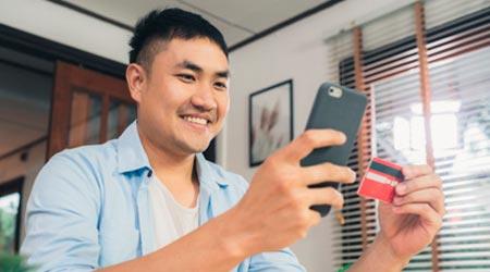homem com celular e cartão de crédito na mão pagando sua terapia feliz