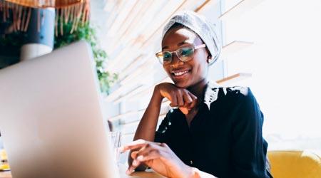 Como ser Terapeuta - Mulher em computador sorrindo com seu Propósito de ser Terapeuta