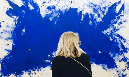 mulher em frente a pintura abstrata índigo