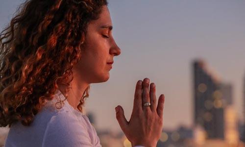 Mulher em Namaste praticando Svadhyaya: a busca por autoconhecimento no Yoga
