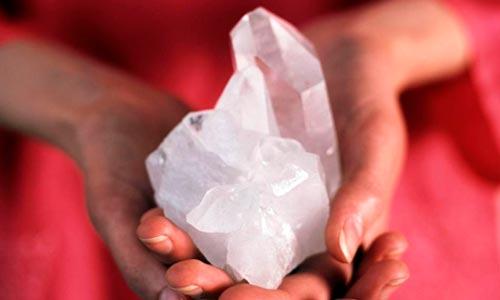 mãos segurando cristais com energia tameana