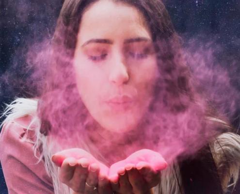 lei da intenção e desejo - foto conceitual de mulher soprando poeira cósmica