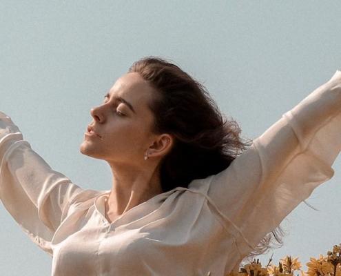 como desenvolver inteligência emocional: mulher em plenitude de braços abertos em campo