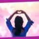 mulher de costas fazendo coração com as mãoes em meditação do amor próprio e autoaceitação