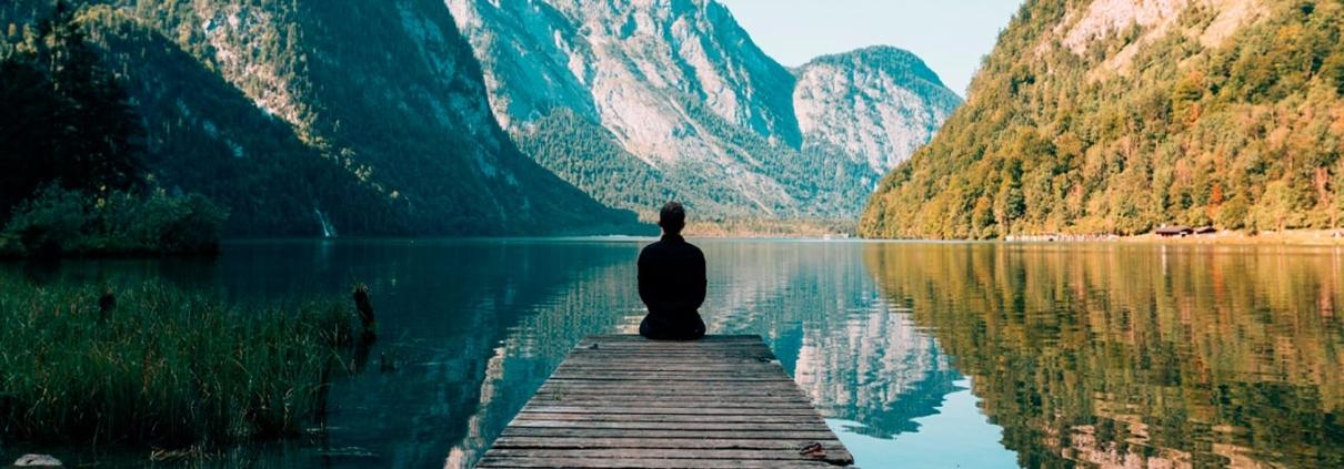 lei do darma: a sétima lei espiritual do sucesso representada por homem sentado a beira de um lago